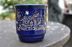 Blue ceramic Christmas mug with an image is on the wooden table. Blue ceramic Christmas mug with the inscription `Advent in Zalzburg` on a wooden table. Photo Stock Images