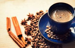Blue ceramic cup with black coffee drink and coffee beans, cinnamon and star anise spices royalty free stock photos