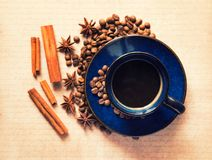 Blue ceramic cup with black coffee drink and coffee beans, cinnamon and star anise spices stock image