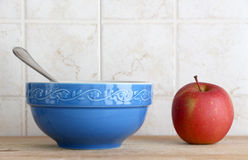 A blue ceramic cup with a spoon and an apple Royalty Free Stock Photography