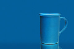 A blue ceramic mug over a blue background Stock Image