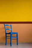 Blue chai. R against a yellow painted wall, in italy Royalty Free Stock Photography
