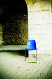 Blue chair. A lone blue chair sits in an open exhibition space Stock Photos