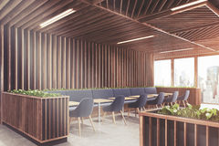 Blue chair cafe wooden interior side toned. Side view of a modern cafe or a coffee shop interior with wooden walls, panoramic windows and dark blue armchairs Stock Photo
