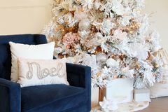 Blue chair and elegant white Christmas tree. royalty free stock image