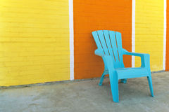 Blue chair in front of a colorful brick wall Royalty Free Stock Images