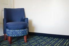 Blue chair in hotel room. Blue chair on patterned carpet in hotel room Royalty Free Stock Image