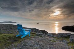 Blue chair, ocean view. The sun sets in a moody sky, as a fishing boat heads home ,in front of a blue chair with ocean view Royalty Free Stock Image