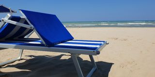 Relax in beach morning. A blue chair for a relax beach morning in a sunny day stock photography
