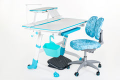 Blue chair, school desk, blue basket, desk lamp and black support under legs Stock Images