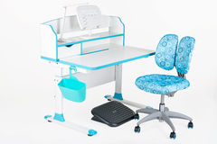 Blue chair, school desk, blue basket, desk lamp and black support under legs Stock Photo