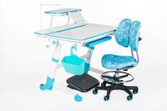 Blue chair, school desk, blue basket, desk lamp and black support under legs Stock Photos