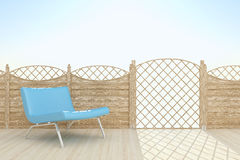 Blue chair and sky. Blue leather chair next to a wooden fence Stock Photos