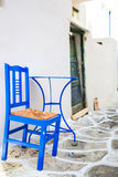 Blue chair and table on street of typical greek traditional village on Mykonos Island, Greece, Europe Stock Photo