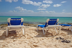 Blue Chair Vista. Empty blue beach chairs on a sandy beach overlook the blue waters of the Caribbean ocean Royalty Free Stock Photography