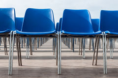 Blue chairs. Empty blue chairs lined up Royalty Free Stock Photo