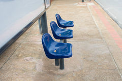 Blue chairs at bus stop Stock Image