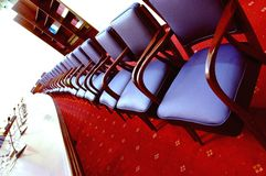 Blue chairs in the conference room. Photo of blue chairs with red carpet in the conference room, business meeting concept Royalty Free Stock Images