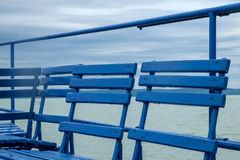 Blue chairs on dock or pier waiting for turist. Cloudy sky cold weather at Balaton lake in the summer season Royalty Free Stock Images