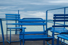 Blue chairs on dock or pier waiting for turist. Cloudy sky cold weather at Balaton lake in the summer season Stock Photos