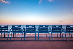 Blue chairs on the Promenade des Anglais in Nice France. Mediterranean Sea and famous blue chais on Promenade des Anglais at sunset in Nice, Cote d`Azur, France stock photos