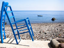 Blue chairs rocky beach Royalty Free Stock Photos
