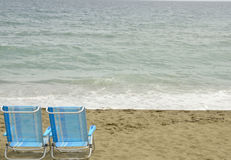 Blue chairs in the shore Royalty Free Stock Images