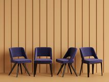 Blue chairs are standing in an empty yellow room with relief stripes on the wall Stock Photos