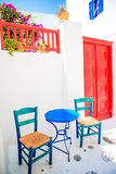 Blue chairs and table on street of typical greek traditional village with white houses on Mykonos Island, Greece, Europe Royalty Free Stock Image