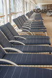 Blue Chaise Lounges LInes up on Cruise Deck. Chaise lounges lined up on the empty deck of a cruise ship stock photos