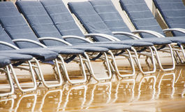 Blue Chaise Lounges on Wet Deck. A line of blue chaise lounges on a ship's deck in the rain royalty free stock image