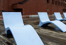 Blue Chaise Lounges on Wood Pier by Brick Building. Modern Blue Chaise Lounge Chairs on a Wood Pier stock photo