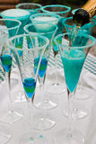 Blue champagne. Champagne being poured into glasses filled with a blue liquor Stock Images