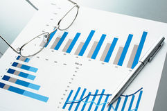 Blue charts, glasses and pen. Stock Photography