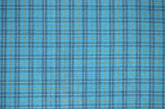 Blue checked fabric texture. Blue checked material with yellow and white lines running through the polyester cotton fabric texture royalty free stock photo