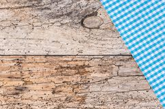 Blue checked tablecloth on old wooden table top. Rustic blue checked table-cloth fabric on old wooden table, top view, copy space Royalty Free Stock Images