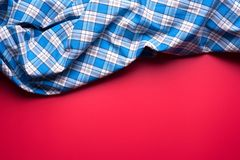 Blue Checkered Fabric on red Background.  Stock Photo