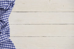 Blue checkered fabric with white wooden background Stock Photography
