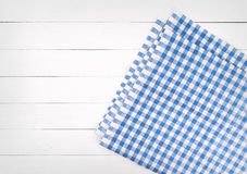 Blue checkered folded tablecloth on white wooden table, top view Stock Images
