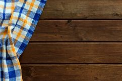 Blue checkered picnic cloth on brown wooden table. stock image