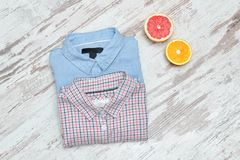 Blue an checkered shirt on a wooden background, halves of citrus. Fashionable concept Royalty Free Stock Photo