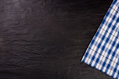 Blue checkered tablecloth on the black stone table with copy space for your text. Top view Royalty Free Stock Photography
