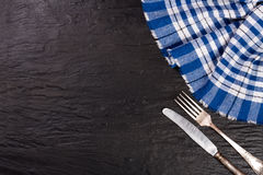 Blue checkered tablecloth on the black stone table with copy space for your text. Top view Royalty Free Stock Image