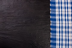 Blue checkered tablecloth on the black stone table with copy space for your text. Top view.  Royalty Free Stock Photo