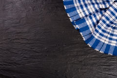 Blue checkered tablecloth on the black stone table with copy space for your text. Top view.  Stock Photography