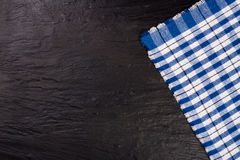 Blue checkered tablecloth on the black stone table with copy space for your text. Top view.  Stock Photo
