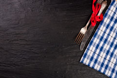 Blue checkered tablecloth on the black stone table with copy space for your text. Top view.  Royalty Free Stock Photos