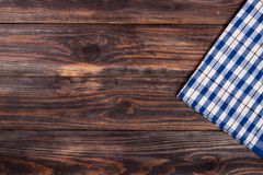 Blue checkered tablecloth on the black wooden table with copy sp. Ace for your text. Top view Royalty Free Stock Photo