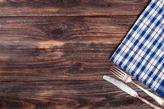 Blue checkered tablecloth on the black wooden table with copy space for your text. Top view Royalty Free Stock Photo
