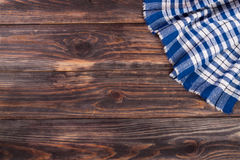 Blue checkered tablecloth on the black wooden table with copy space for your text. Top view.  Stock Images
